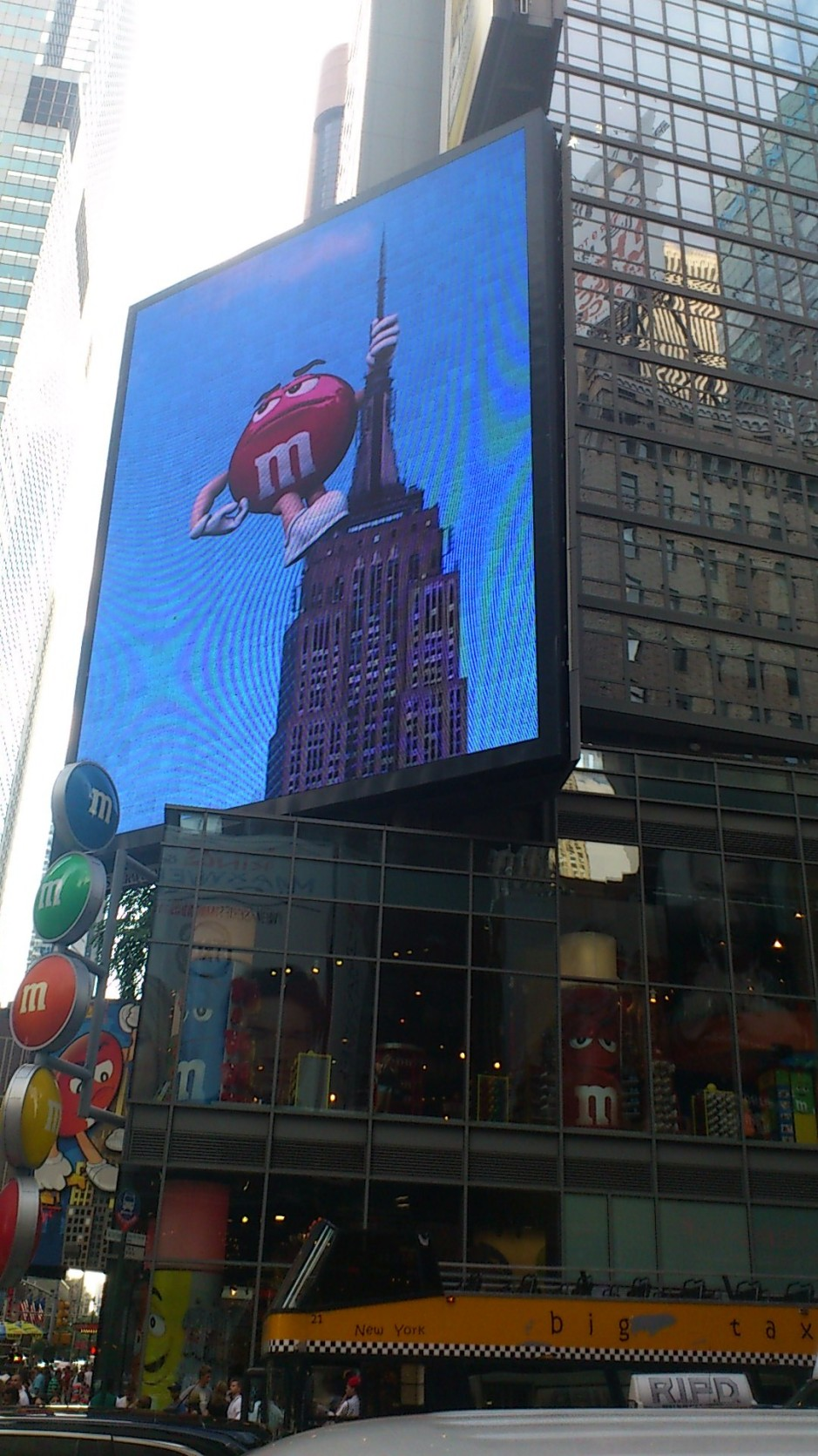 The red M & M's chocolate cartoon character climbs the Empire State Building. All displayed on a huge video screen at the M & M's World in Times Square, New York City