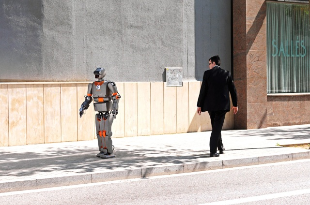 Robot passes a man on a street; man stares