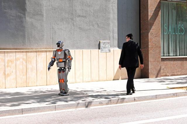 Robot passes a man on a street; man stares